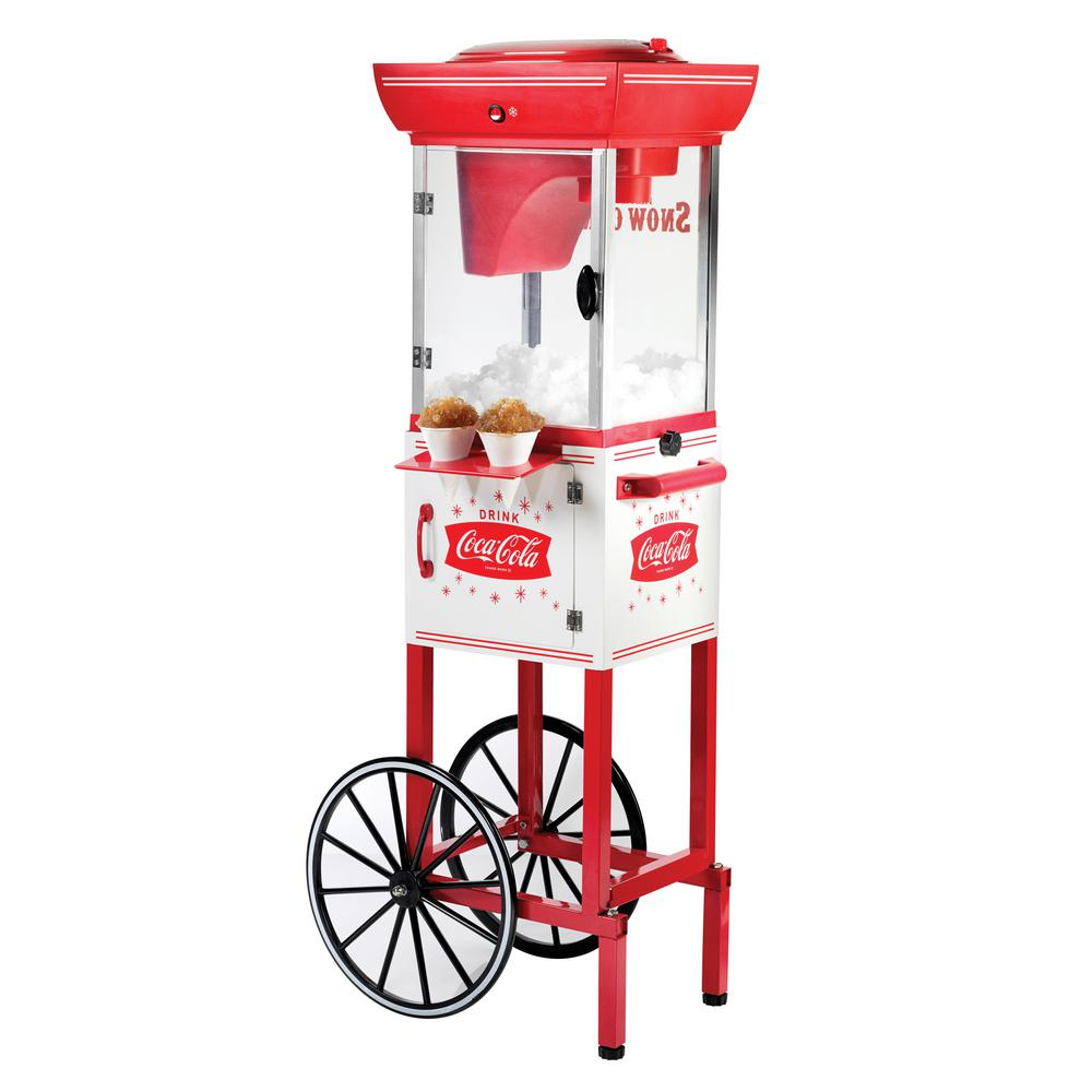 Nostalgia Coca-Cola Cart Snow Cone Maker, Red/White The Nostalgia SCC399COKE 4-Foot Tall Coca-Cola Snow Cone Cart will be the hit of every party! Add ice to the shaving cage and turn the unit on, watch as the deluxe shaving system transforms ice into a delicious snow cone. The storage compartment allows for snow cone supplies be organized and ready for serving. Color: Red/White.