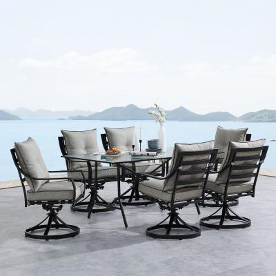 Lavallette 7-Piece Steel Outdoor Dining Set with Silver Linings Cushions, Swivel Rockers and a Glass-Top Table