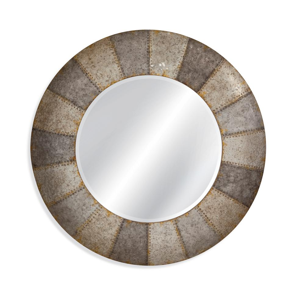 BASSETT MIRROR COMPANY Noris Decorative Wall Mirror The Noris wall mirror has a circular shape and bolted aged aluminum finish. The aluminum finish is a two tone shade of metal with a distressed matt finish. Perfect for many different room setting.