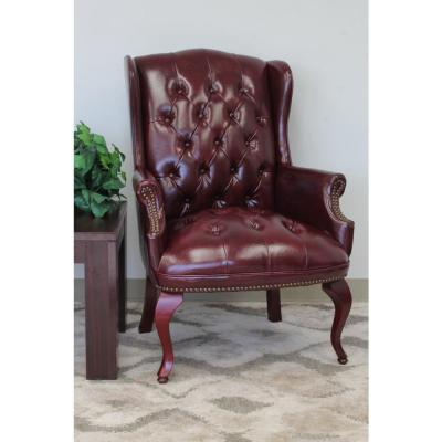 Wing Back Chair. Burgundy Vinyl. Mahogany Finish. ButtonTufted. Brass Nail Heads.