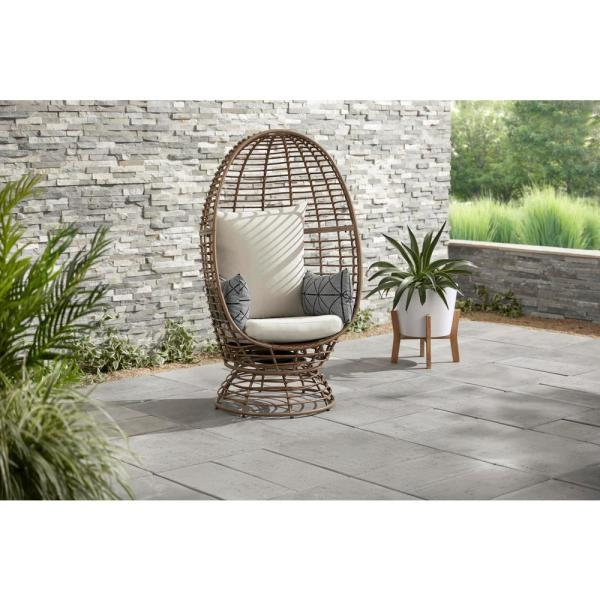 Brown Wicker Outdoor Swivel Patio Egg Lounge Chair with Beige Cushions and Black/Cream Pattern Pillows