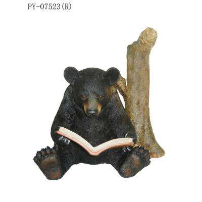 Black Bear Sits Reading by Tree Trunk Statue