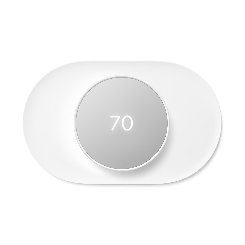 """Google Nest Thermostat Snow + Nest Thermostat Trim Kit Snow Pair a Google Nest Thermostat with the Nest Thermostat Trim Kit for a perfect match. The Nest Thermostat is the helpful thermostat with a cozy price. It can turn itself down to save energy when you leave the house. You can control it from anywhere with the Google Home app – whether you're on an errand or on vacation. You can even change the temperature without getting off the couch or out of bed. Just say, """"Hey Google, turn up the heat.""""1 The Nest Thermostat Trim Kit is designed to cover imperfections on the wall from removing your old thermostat. Color: Snow."""