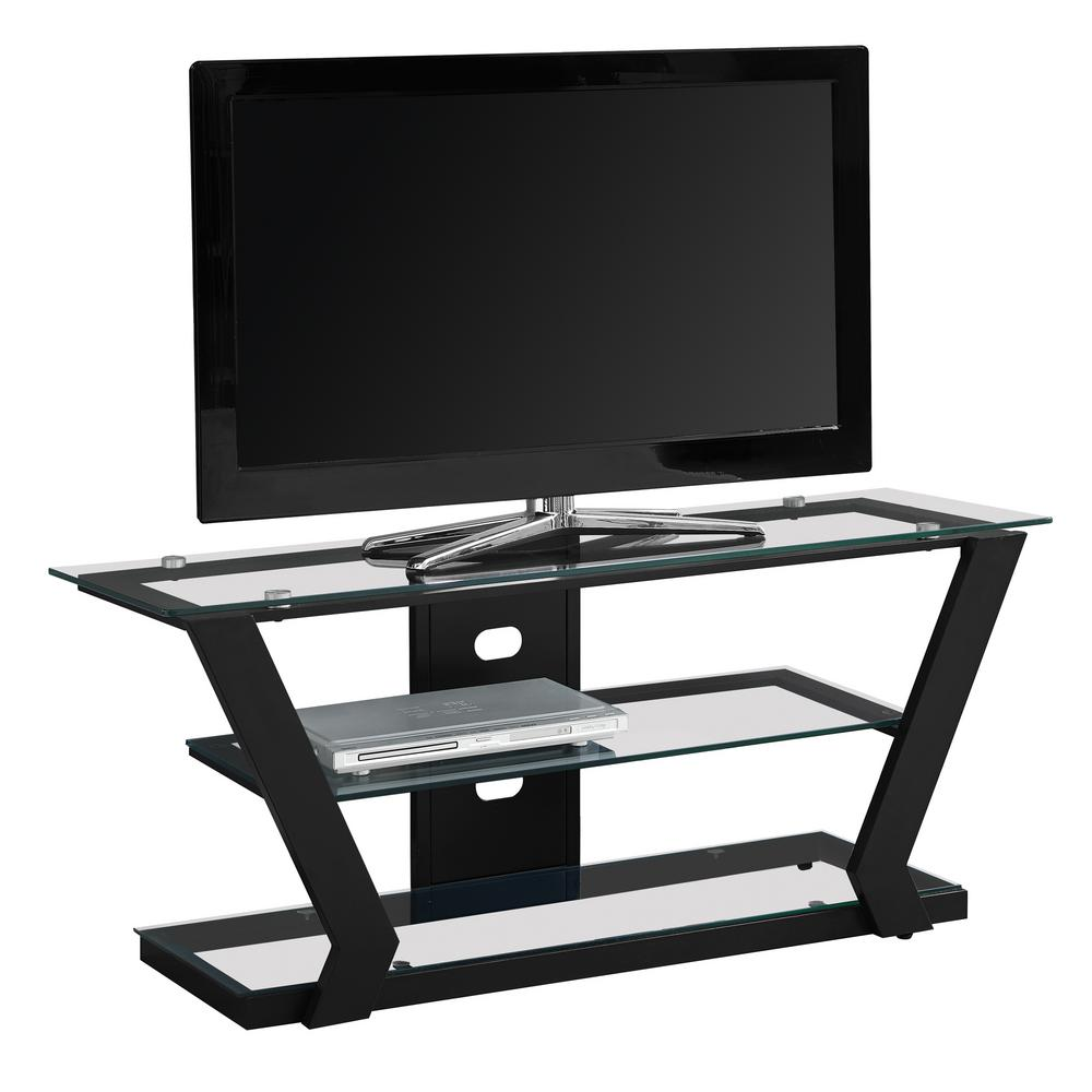 MONARCH SPECIALTIES Glass TV Stand with Black Metal Modernize your space with this contemporary black metal TV stand that accommodates all TV sizes with a center stand. Featuring solid, durable tempered glass shelves and a sleek black metal frame, this TV console will fit perfectly in your living room, den, TV room or basement. The chic angled design of the frame gives a clean, sophisticate look while you entertain your guests. With ample surface area for all of your entertainment accessories and a convenient cord management system to reduce unsightly wires this TV stand will have you organized in no time.