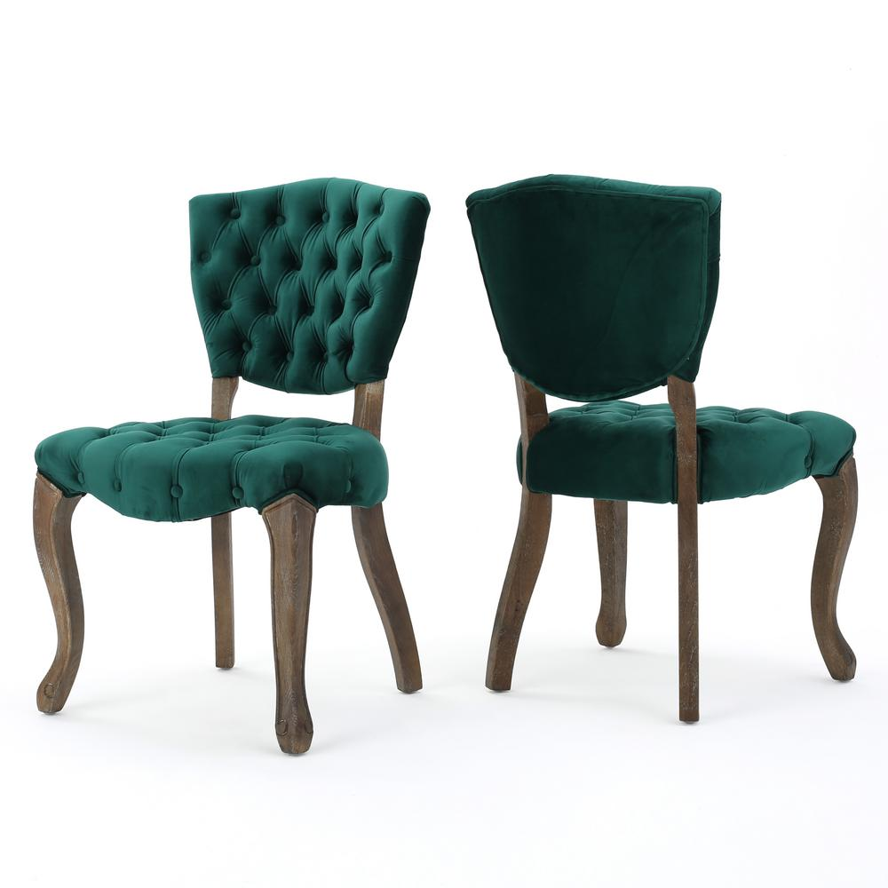 Noble House Bates Dark Green Velvet Dining Chairs (Set of 2) For a European inspired design, look no further than these tufted dining chairs. This set of two chairs offers ample tufting, a solid frame, and intricately carved wooden legs. These chairs feature a dark green finishing.