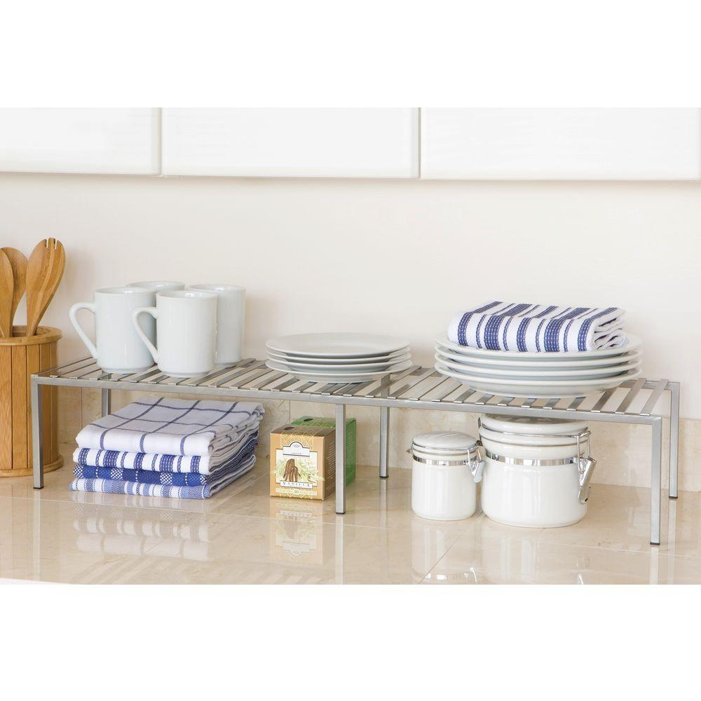 Seville Classics Expandable Kitchen Counter and Cabinet Shelf, White Organize your kitchen counter or cabinet shelves with this expandable kitchen shelf. Shelf adjusts from 15.75 in to 30 in W to fit your storage needs. Constructed of iron for strength and finished in platinum powder-coat for protection against corrosion in dry environments.