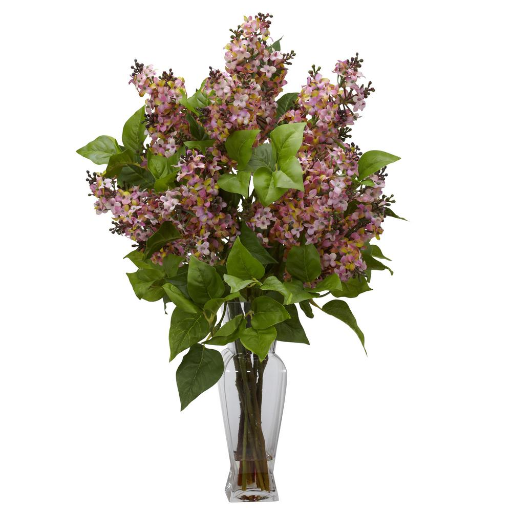 Nearly Natural 24 in. Lilac Silk Flower Arrangement in Pink Lilacs are amongst the most colorful of flowers, and we've captured that perfectly with this Nearly Natural re-creation of lilacs in full bloom. Yes, you won't be able to smell them, but they look so perfectly real, with delicate, colorful petals adorning stout branches with green leaves, that you won't mind one bit. This colorful collection is gathered in a glass vase with liquid illusion, making it the perfect adornment for a table, counter, or desk.